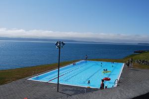 Im Vordergrund ist ein Pool auf einer Klippe, im Hintergrund das weite Meer.