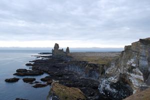 Eine schroffe, zerklüftete Küstenlinie erstreckt sich durchs Bild. Die Felsen sind schwarz und rau, kleinere Felsbrocken ragen aus dem Meer.