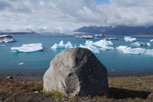 Im Vordergrund des Bildes sieht man einen Felsen, der ein bisschen wie ein lächelndes Gesicht aussieht. Im Hintergrund erstreckt sich ein weiter See mit großen, treibenden Gletscherstücken.