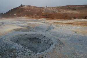 Im Vordergrund ist ein Loch mit kochendem Schlamm. Im Hintergrund erstreckt sich eine Vulkankette. Die Erde ist rot und gelb, es riecht stark nach Schwefel.