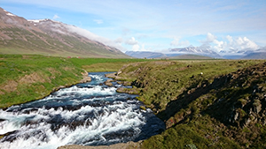 Man sieht einen breiten, reißenden Fluss in einer grünen Ebene. Im Hintergrund erheben sich imposante Berge.