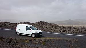Ein kleiner, weißer Campervan vor einer Ebene mit schwarzem Lavageröll