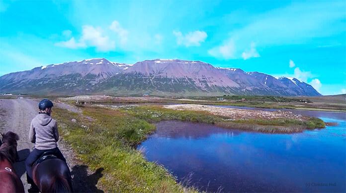 Ein Bild von Christinas Helmkamera: man sieht Hlín auf ihrem Pony, sie schaut nach rechts über einen weiten, stillen See. Im Hintergrund sieht man die hohen Berge.