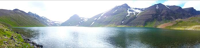Ein weiter, stiller See umgeben von schneebedeckten Bergen.