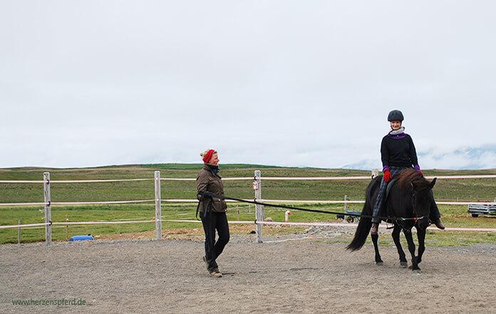 Sitzschule in Island: Christina sitzt auf einer schwarzen Stute und lässt ihre Füße kreisen. Hlín steht in der Mitte und gibt Anweisungen. Im Hintergrund sieht man die weitläufigen Koppeln von Lynghorse.