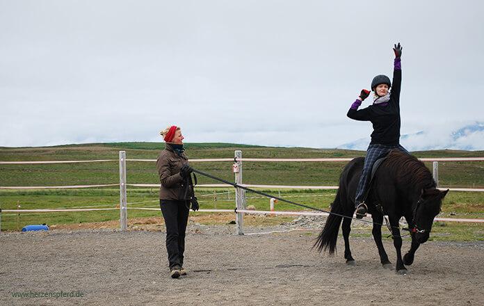 Sitzschule in Island: Christina sitzt auf einer schwarzen Stute und greift mit ihrer rechten Hand weit nach oben über ihren Kopf. Hlín steht in der Mitte und gibt Anweisungen. Im Hintergrund sieht man die weitläufigen Koppeln von Lynghorse.