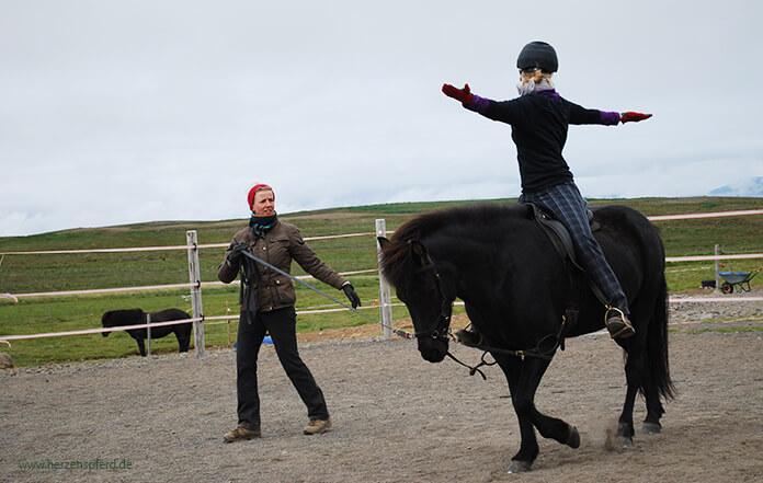 Sitzschule in Island: Christina sitzt auf einer schwarzen Stute und dreht ihren Oberkörper mit weit ausgestreckten Armen nach rechts. Hlín steht in der Mitte und gibt Anweisungen. Im Hintergrund sieht man die weitläufigen Koppeln von Lynghorse.