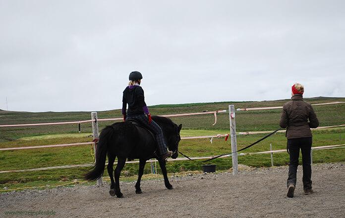 Sitzschule in Island: Christina sitzt auf einer schwarzen Stute und zieht gerade die Schultern hoch. Hlín steht in der Mitte und gibt Anweisungen. Im Hintergrund sieht man die weitläufigen Koppeln von Lynghorse.