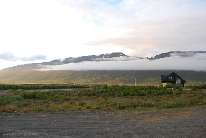 Isländisches Haus auf der Ebene, im Hintergrund das wolkenverhangene Hochland