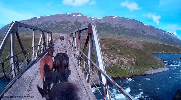 Reiterin mit Handpferd überquert einen Gletscherfluss im Skagajord, Island