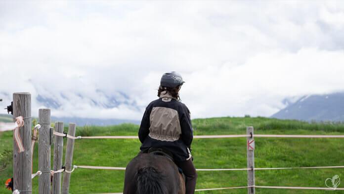 Eine Reiterin auf einem schwarzen Islandpferd. Sie reitet auf einem Platz inmitten grüner Wiesen, im Hintergrund sind wolkenverhangene Berge zu sehen.