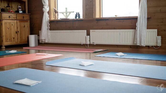 Bunte Yogamatten auf einem Holzboden innerhalb eines hohen, hellen Raums.