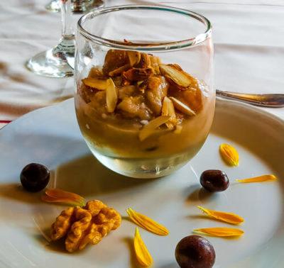 Angeforenes Birnen-Nuss-Kompott mit Mandeln, Walnüssen und Schokolinsen, angerichtet mit Blütenblättern.