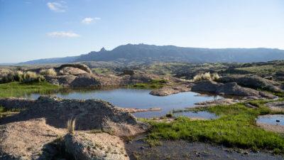 Ein kleiner Teich zwischen Felsbrocken, im Hintergrund eine Bergkette, die wie ein schlafender Riese aussieht.