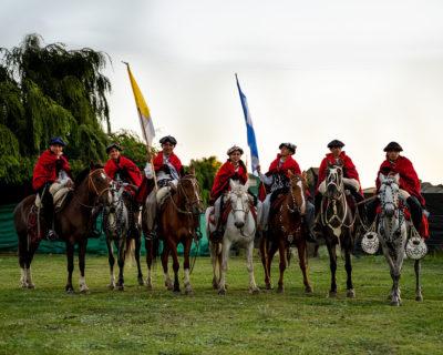 Eine Grupper junger Gauchos in traditioneller Kleidung auf ihren Pferden.