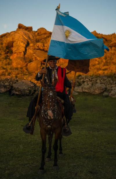 Der älteste Gaucho (78) des Festivals auf seinem Pferd mit einer großen, wehenden Argentinien-Flagge in der Hand.