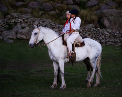 Eine junge Frau (Ramons Tochter) in traditioneller Gaucho Kleidung auf einem weißen Pferd.