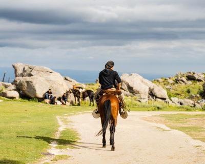Ein junger Reiter auf dem Weg zu seinen Freunden, die man im Hintergrund an einem großen Felsen sitzen sieht, ihre Pferde neben ihnen.
