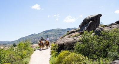 Eine Gruppe Reiter neben einem Felsbrocken, der weit über ihre Köpfe reicht.