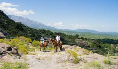 Zwei Reiter genießen den Ausblick auf dem Weg in die Berge.